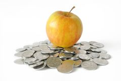 Apple and coins heap Stock Photography
