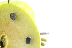 Apple a collé avec les clous, détail d'un fruit avec du fer, outil image libre de droits