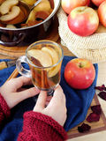 Apple compote. Female hands are holding a glass of warm compote Royalty Free Stock Photos