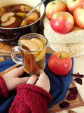 Apple compote. Female hands are holding a glass of warm compote Royalty Free Stock Photo