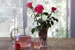 Apple compote in a transparent jug, a bouquet from roses and fre Royalty Free Stock Photos