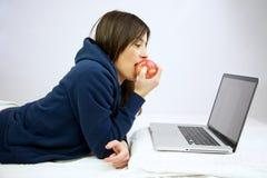 Apple Computer που τρώει την μπροστινή κόκκινη γυναίκα Στοκ Φωτογραφία