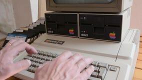 Apple Computer envejecido y manos que mecanografían en el teclado metrajes