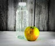 Apple con la botella de agua para entrenar Imágenes de archivo libres de regalías