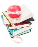 Apple con la cinta de la medida en la pila grande de libros fotografía de archivo libre de regalías