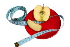 Apple con la misura di nastro sul piatto rosso Fotografia Stock Libera da Diritti
