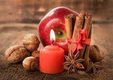 Apple con las nueces, el anís de estrella, el canela y una vela Fotos de archivo