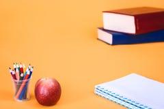 Apple con los lápices y los libros de escuela en fondo anaranjado fotografía de archivo libre de regalías