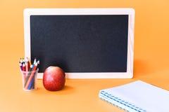 Apple con los l?pices y consejo escolar en fondo anaranjado fotografía de archivo