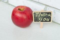 Apple con un agradecimiento usted inscripción en un fondo del negro del tablero de madera Imagen de archivo