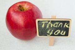 Apple con un agradecimiento usted inscripción en un fondo del negro del tablero de madera Foto de archivo libre de regalías