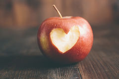 Apple con un cuore lo incide fotografie stock
