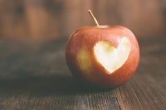 Apple con un cuore lo incide immagine stock