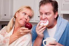 Apple contra a decisão saudável comer da filhós Fotografia de Stock Royalty Free