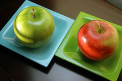 Apple contrast. Red and green apples on green and blue plates Royalty Free Stock Image