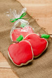 Apple cookies on burlap. Red apple shaped sugar cookie cut-outs rest on a piece of burlap. One is packaged up for a gift in plastic with a green bow Royalty Free Stock Photo