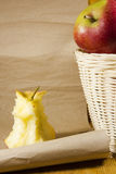 Apple core and a basket with apples Stock Photo