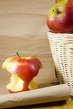 Apple core and a basket with apples Royalty Free Stock Photography