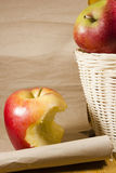Apple core and a basket with apples. On the background paper scroll stock photography