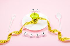 Apple core with measuring tape in place of the waist on a white plate with text MY DIET on pink background. Diet, weigh loss,. Starvation, fitness concept stock photography