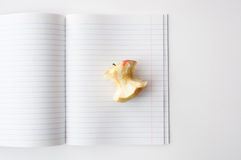 An Apple core in the open notebook in line Stock Image