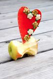 Apple core and a red carton heart Royalty Free Stock Images