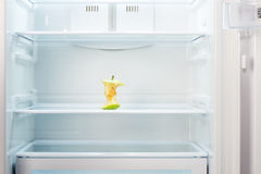 Apple core on shelf of open empty refrigerator Royalty Free Stock Image
