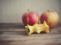 Apple core. An apple core with two whole apples on the background. Vintage film style applied Stock Photography
