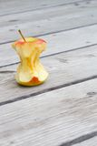 An apple core. On a wooden surface Stock Photography