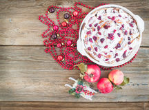 Apple, cranberry and cinnamon roll cake with creamy icing and Ch. Ristmas decoration over a rustic wood background with a copy space Royalty Free Stock Images