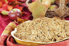Apple Crisp. Freshly baked apple crisp with fresh apples and autumn leaves in the background. Shallow depth of field with selective focus on the foreground royalty free stock image