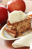 Apple Crisp. A plate with apple crisp, vanilla ice cream, cinnamon sticks, and apples in the background stock images