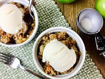 Apple crisp with ice cream. Apple crisp with vanilla ice cream in ramekins royalty free stock images