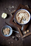Apple crumble with almonds and amaretto biscuits on rustic table with wood frames and spoons Royalty Free Stock Image