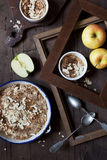 Apple crumble with almonds on rustic table with wood frames and spoons Royalty Free Stock Images