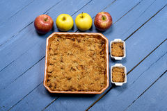 Apple crumble on a blue wooden table. Crumble on a wooden table painted blue royalty free stock photo