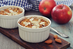 Apple crumble. In ceramic molds with fresh apples on wooden background Stock Photo