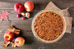 Apple crumble pie, overhead scene against dark wood. Apple crumble pie, top view scene against a dark wood background. Homemade autumn dessert stock images