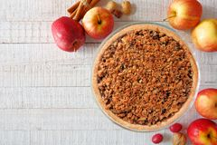Apple crumble pie, overhead scene on white wood. Apple crumble pie, overhead scene on a white wood background. Homemade autumn dessert royalty free stock images