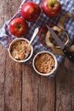 Apple crumble in portion pots on the table. vertical top view Stock Image