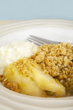 Apple Crumble and Whipped Cream. A bowl full of delicious home made apple rhubarb crumble with whipped cream. This crumble is made with wholemeal flour and Stock Photo