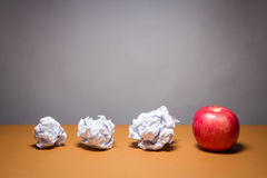An apple and crumpled paper. Business frustrations, Job stress and Failed exam concept. Royalty Free Stock Images