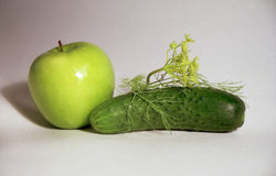Apple, cucumber and fennel. Green apple with patch of light, dim cucumber and withered branch of fennel with blossoms Royalty Free Stock Photo