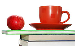 Apple, cup and books Stock Photos