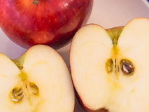 Apple cut in half with seeds and pulp to show. Red and fresh apple, cut in half with seeds and pulp the show, tasty and delicious health food Stock Photo