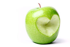 Apple with cut off heart shape. Royalty Free Stock Photos