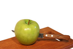 Apple on cutting board Stock Images