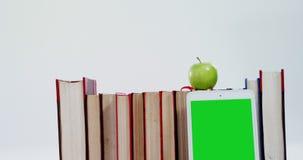 Apple, cyfrowa pastylka i książki na białym tle, zbiory