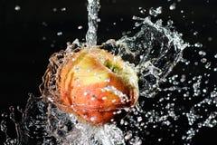 Apple dans l'eau éclabousse sur le fond noir Image libre de droits