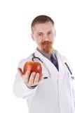 Apple dans une main du docteur Photo stock